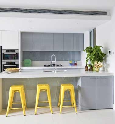El capricho y la alegría del amarillo calienta la decoración gris y blanca de la cocina.  Frentes y aparadores lacados en gris y blanco en un dúo elegante, iluminan la habitación