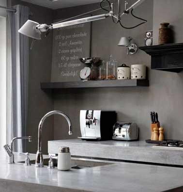 Una cocina gris 100% industrial con hormigón encerado taupe en las paredes.  La encimera y el fregadero de piedra brillante iluminan las tonalidades de gris