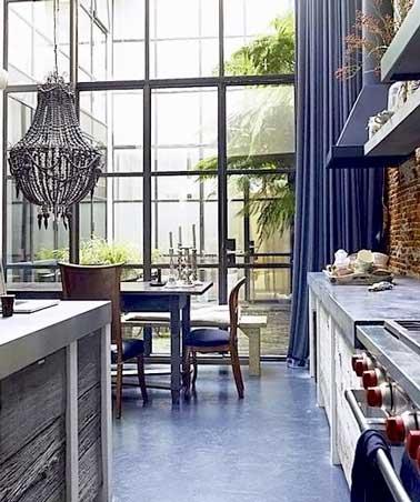 La cocina de hormigón encerado gris topo y el color azul se combinan en esta sala industrial.  La pared de ladrillo rojo, la lámpara de araña barroca gris y la isla de aluminio hacen que la decoración