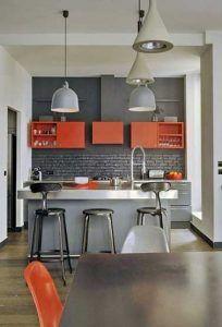 Los muebles y sillas naranjas despiertan la cocina gris.  Las paredes blancas, la isla de aluminio de estilo industrial y los accesorios de iluminación juegan con los brillantes contrastes con el gris.