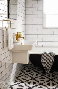 Azulejos y loza en blanco y negro, accesorios de latón, bañera independiente, agregue una dosis de ropa de baño a juego, el cóctel decorativo perfecto para un baño retro